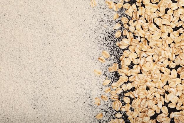 Gruau moulu à la farine d'avoine biologique et flocons d'avoine éparpillés sur une table sombre fond d'aliments naturels