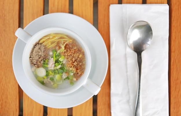 Gruau de riz à la bouillie traditionnelle de thaïlande en coupe sur une table en bois avec une cuillère et des tissus.