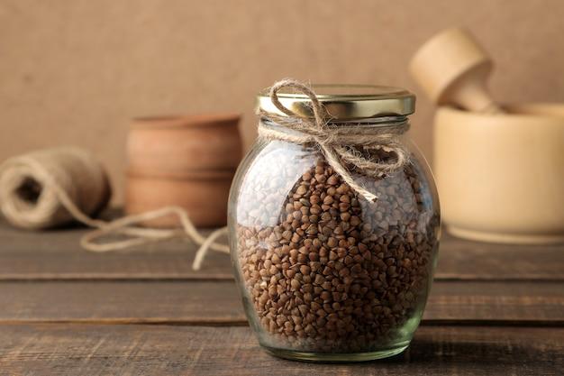 Gruau de sarrasin sec dans un bocal en verre au premier plan sur une table en bois marron. des céréales. nourriture saine. bouillie.