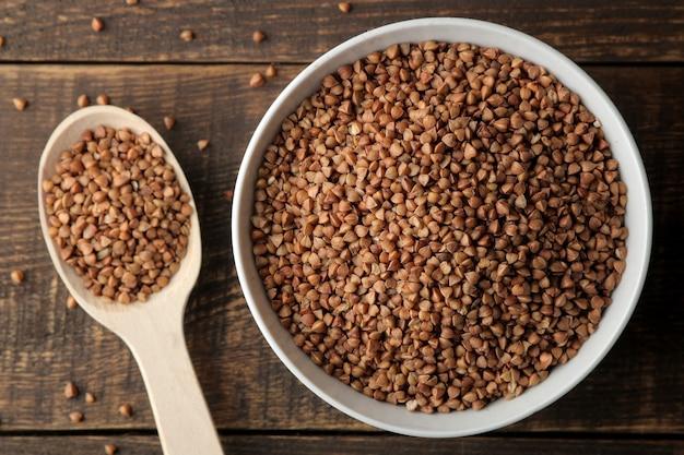 Gruau de sarrasin sec dans un bol blanc avec une cuillère sur une table en bois marron. des céréales. nourriture saine. bouillie. vue de dessus