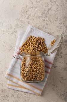 Gruau de soja entier produit stable sur le plateau. aliment végétarien, le soja est une source de protéines. grains de soja dans un bocal en verre sur béton gris.