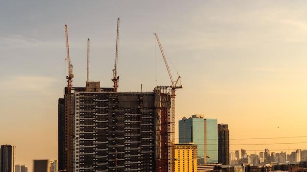 Grue et chantier de construction travaillant sur un complexe de bâtiments au coucher du soleil, développement du concept de ville