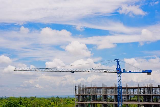 Grue sur chantier et nuage blanc avec fond de ciel bleu