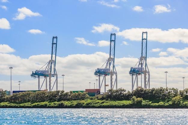 Grue de chargement portuaire et conteneur sur fond de ciel bleu, prêts pour l'expédition