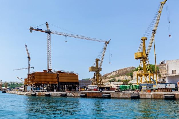 Une grue colorée est placée sur un quai flottant dans le port, à malte. seascape avec vue sur la technique industrielle.