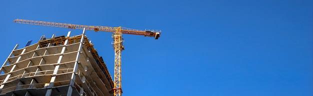 Grue de construction sur un chantier de construction d'immeubles de grande hauteur, fond de ciel bleu, bannière avec photo espace copie