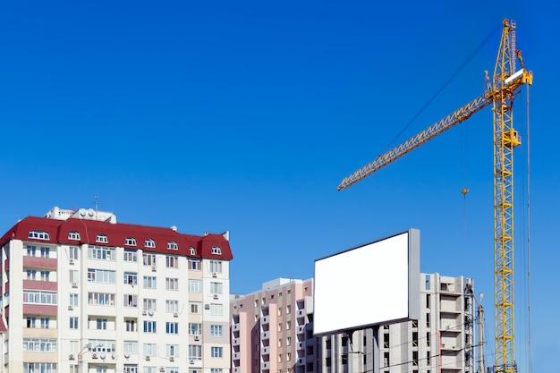 Grue de construction près de maisons construites.
