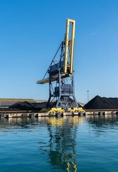 Grue portuaire entourée de charbon