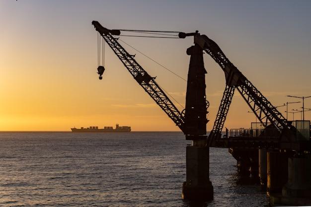 Grue de quai vergara avec un navire derrière au coucher du soleil
