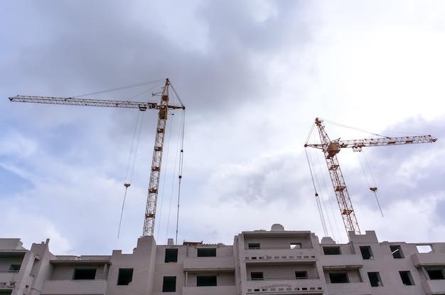 Grue à tour et bâtiment en construction contre le ciel bleu. copiez la photo de l'espace de la construction