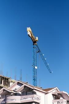 Grue à tour sur le chantier de construction d'un immeuble moderne sur fond de belle maison