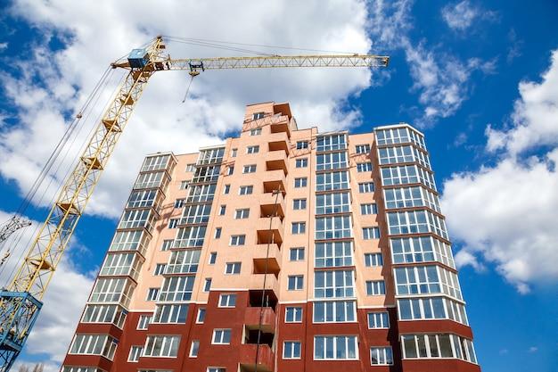 Grue à tour, construction d'un nouvel immeuble moderne sur un fond de ciel bleu nuageux à la journée ensoleillée.