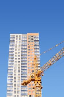 Grue à tour et un immeuble résidentiel de plusieurs appartements nouvellement construit contre le ciel bleu