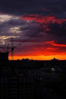 Grue à tour pendant le coucher du soleil de la ville