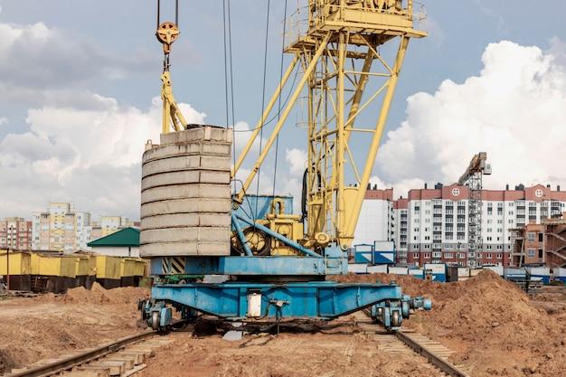 Grue à tour sur rails en gros plan sur le chantier de construction sur fond de ciel nuageux. gros plan sur des équipements de construction lourds pour le levage et le déplacement de charges. grue de chantier.