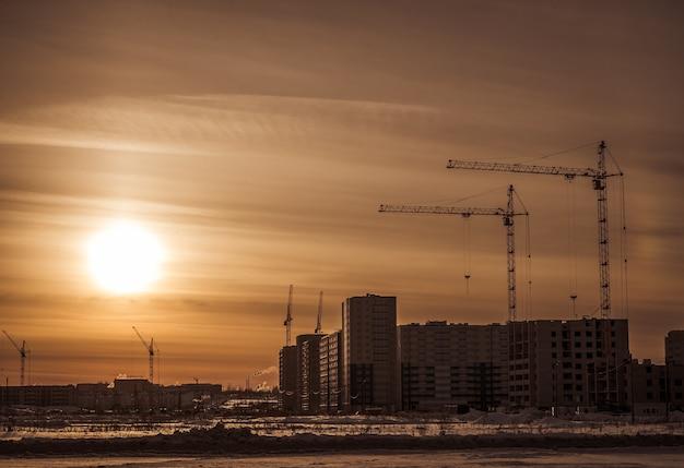 Grues et chantier de construction contre le ciel du coucher du soleil.