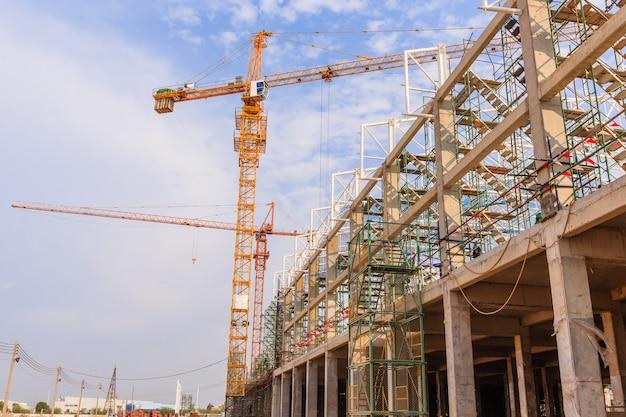Grues de construction industrielle et bâtiment dans un magnifique fond de ciel bleu