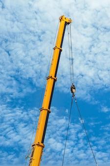 Grues de construction mobiles à bras télescopiques jaunes et grandes grues à tour avec nuages blancs et ciel bleu profond.