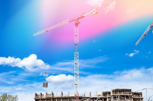 Les grues de construction travaillent sur le site de création sur fond de ciel bleu. vue de dessous de la grue industrielle. concept de construction d'immeubles d'habitation et de rénovation de logements. espace de copie
