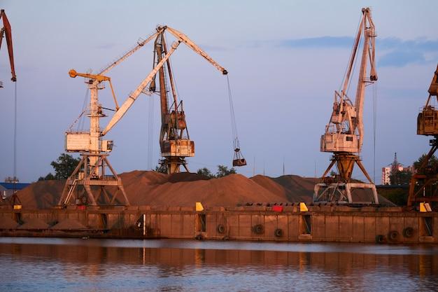 Des grues de manutention en vrac à basculement chargent du sable sur une barge à cargaison sèche dans un port fluvial dans la lumière du soir