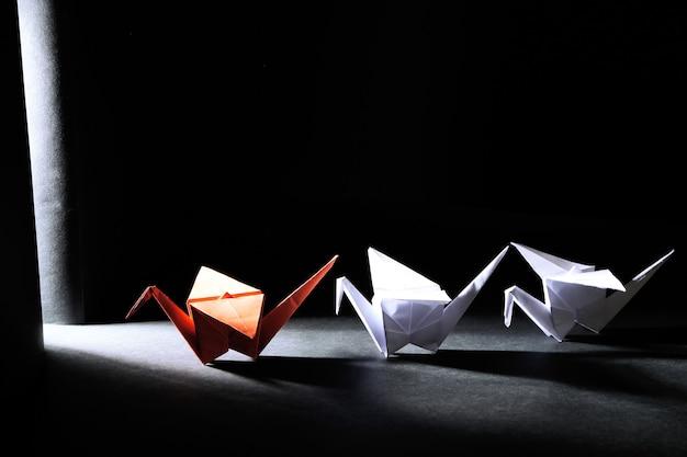 Grues d'origami sur l'obscurité avec la lumière