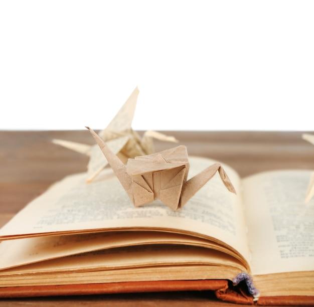 Grues en origami sur vieux livre sur table en bois, sur blanc