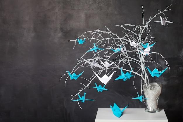 Grues en papier origami sur les branches