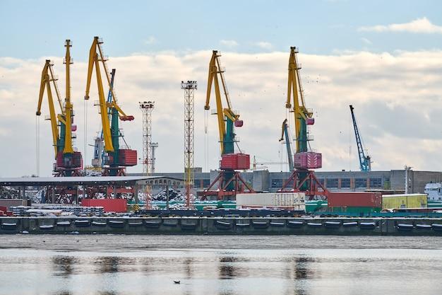 Grues portuaires massives dans le port maritime. grues à quai pour charges lourdes dans le port, parc à conteneurs, terminal de porte-conteneurs. affaires et commerce, logistique. scène industrielle d'hiver.