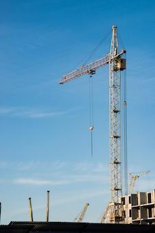 Grues à tour grandes au-dessus des bâtiments en construction contre le ciel bleu.