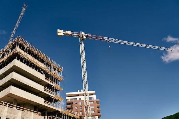 Les grues à tour se tiennent sur le chantier de construction