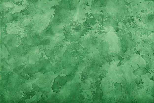 Grunge vert pastel fané vieilli inégale daub plâtre mur texture de fond avec des taches et des coups de peinture, gros plan