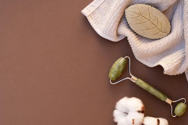 Gua sha, rouleau de massage du visage en pierre naturelle, concept de spa à domicile, arrière-plan de tons de terre, espace de copie