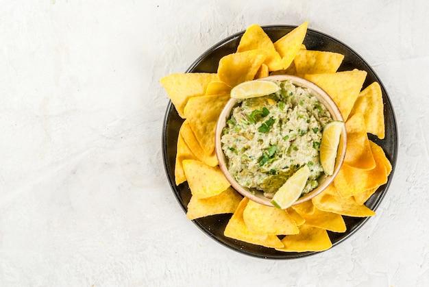 Guacamole fait maison dans un bol, servi avec des nachos