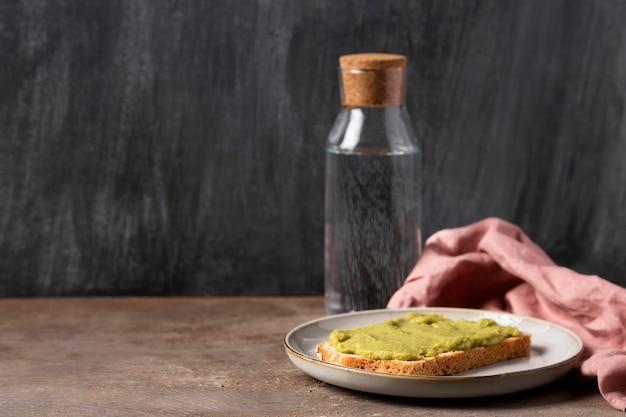 Guacamole sur pain et bouteille d'eau