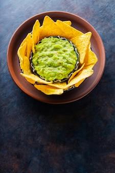 Guacamole sauce mexicaine traditionnelle avec chips tortilla dans un bol en argile. bol de guacamole avec chips de nachos sur fond sombre. espace de copie. vue de dessus