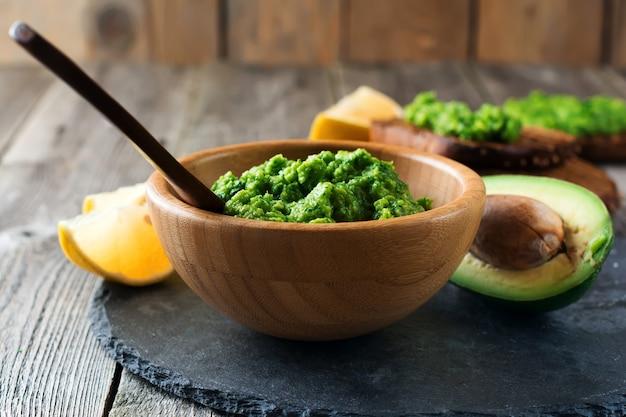 Guacamole sauce mexicaine traditionnelle dans un bol en bambou, citron et couper la moitié de l'avocat sur la vieille surface en bois. mise au point sélective. lieu de texte.