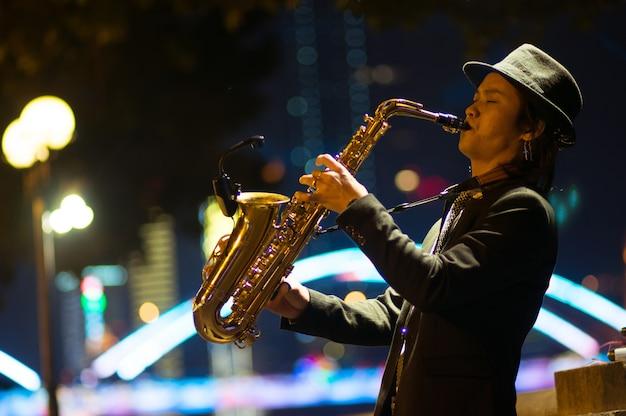 Guangzhou, chine - 15 mars 2016: homme jouant du saxophone dans la rue dans la soirée