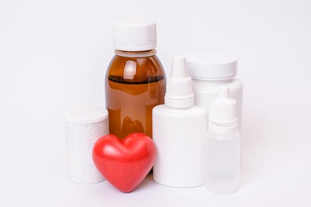 Guérir la place du modèle de modèle de dose de remède pour le concept d'ischémie d'infarctus du myocarde de texte. la photo en gros plan de nombreux contenants en plastique en bouteille avec des comprimés de médicaments petit coeur isolé sur une surface blanche