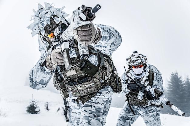 Guerre des montagnes arctiques d'hiver. action par temps froid. paire d'armes des forces spéciales en forêt quelque part au-dessus du cercle polaire arctique, low angle view