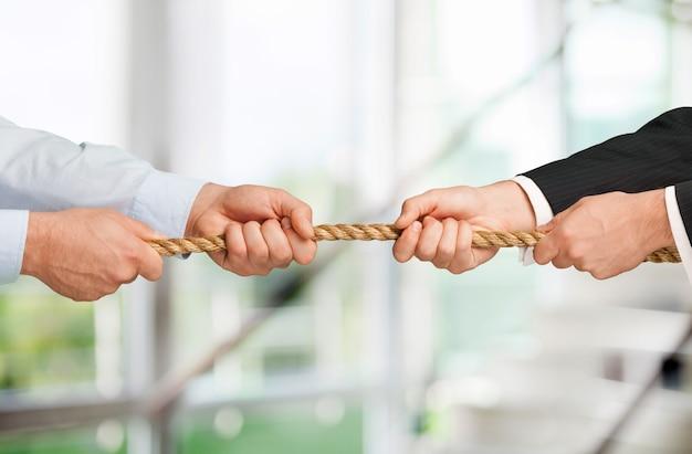 Guerre de remorqueur, deux hommes d'affaires tirant une corde dans des directions opposées