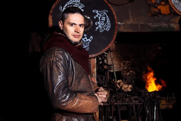 Guerrier viking se tenir dans sa vieille maison près du feu avec une arme.