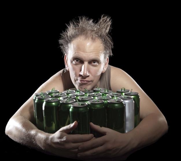 Gueule de bois l'homme ivre et il y a beaucoup de canettes de bière vides