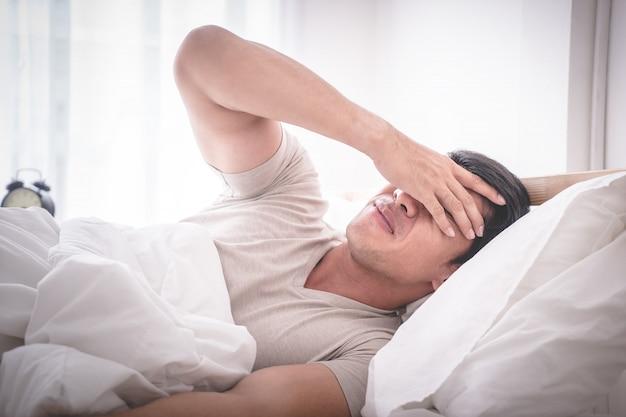Gueule de bois sans sommeil homme sur le lit se réveilla avec mal de tête