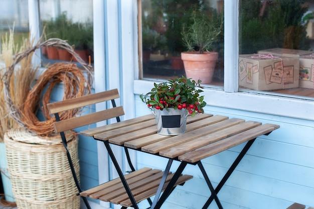 Gui de noël avec berrys rouges en pot sur table en bois. maison sur terrasse maison