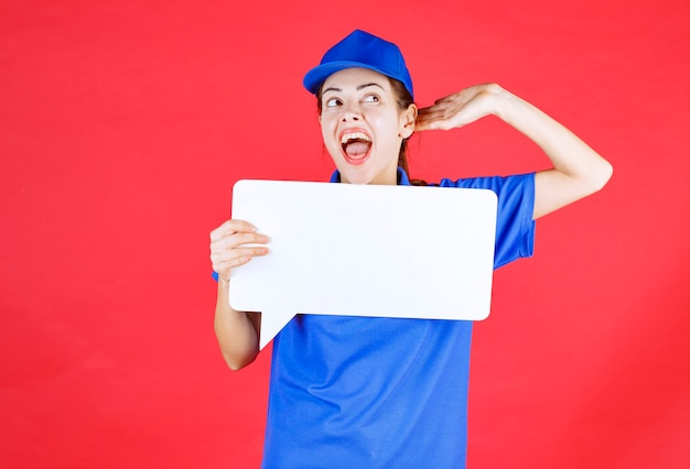 Guide féminin en uniforme bleu tenant un panneau d'information rectangulaire blanc et ouvrant les oreilles et criant.