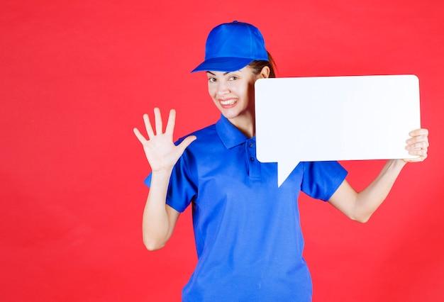 Guide féminin en uniforme bleu tenant un panneau d'information rectangulaire blanc et saluant les participants.