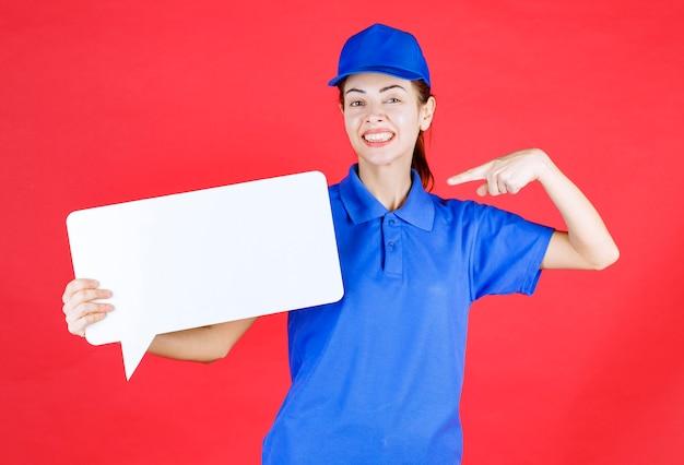 Guide féminin en uniforme bleu tenant un panneau d'information rectangulaire blanc.