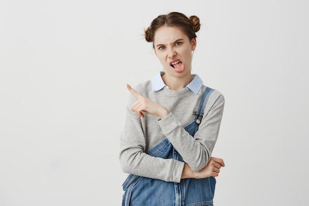 Guillerette femelle adulte montrant le doigt sur le mur blanc. femme confiante avec double chignon mettant la langue dehors et exprimant ne pas aimer son choix. espace copie