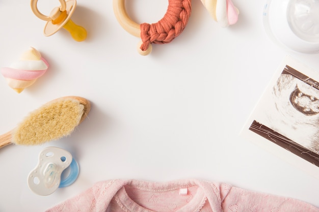 Guimauve; body bébé rose; brosse; sucette; bouteille de lait et jouet sur fond blanc