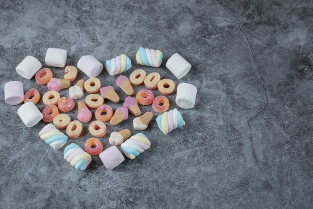 Guimauve et bonbons isolés sur marbre.